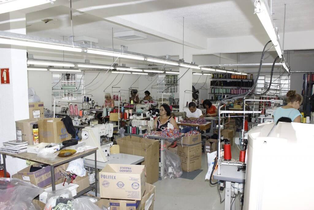 Confecção de costura com funcionarias costurando biquínis